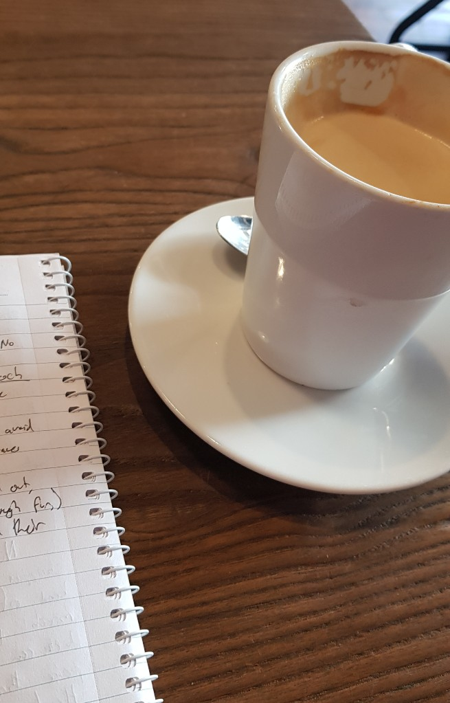 A mug of coffee on a table next to a notebook.