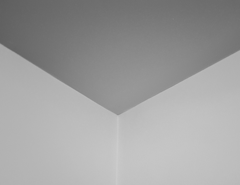 A black and white photo of a ceiling with no cornice.