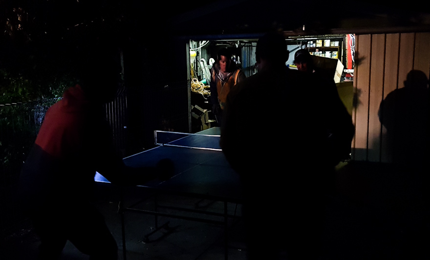 Table tennis doubles being played in a dark driveway.
