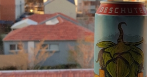 A big can of PNW on a windowsill overlooking buildings.